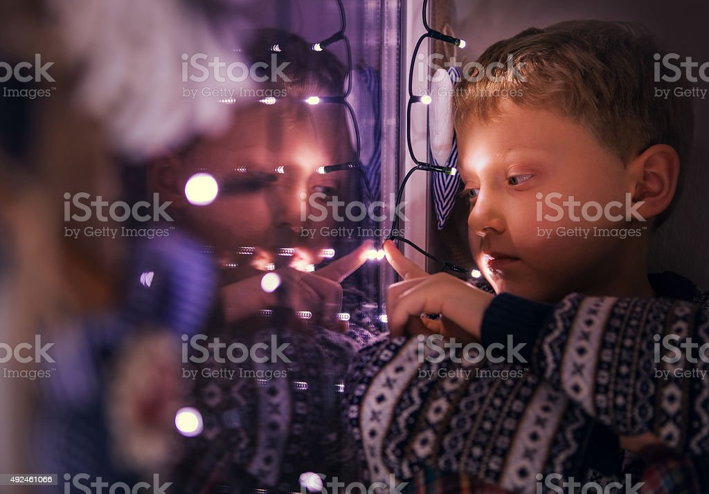 Closeup portrait boy sitting on the window with Christmas Lights stock photo