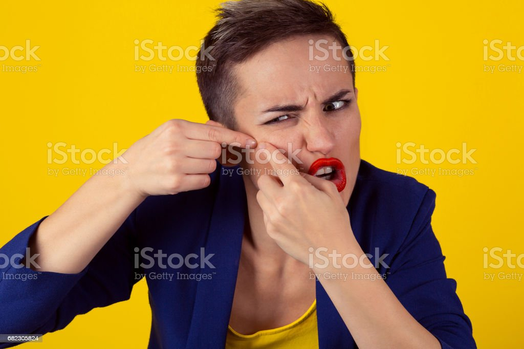 Closeup Portrait frustrated young business woman has find problems with the skin, squeezing a pimple on her cheek isolated yellow background. Negative human emotion, face expression, body language stock photo