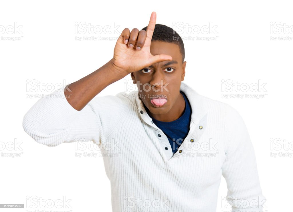 Closeup portrait, funny young man showing loser sign on his forehead and looking at you with disgust stock photo