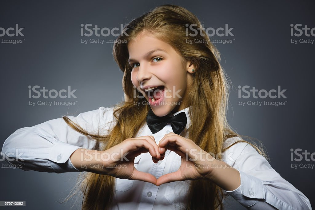 Closeup portrait happy girl shows hands in shape of heart stock photo