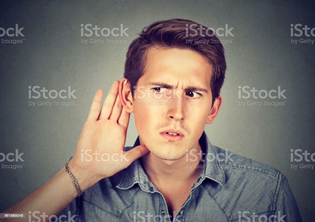 Closeup portrait hard of hearing man placing hand on ear stock photo