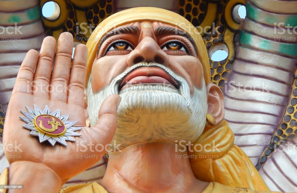 Closeup portrait of 54 feet high Shiridi SaiBaba statue in blessing pose under hood of five headed snake in a temple, Machilipatnam,India stock photo
