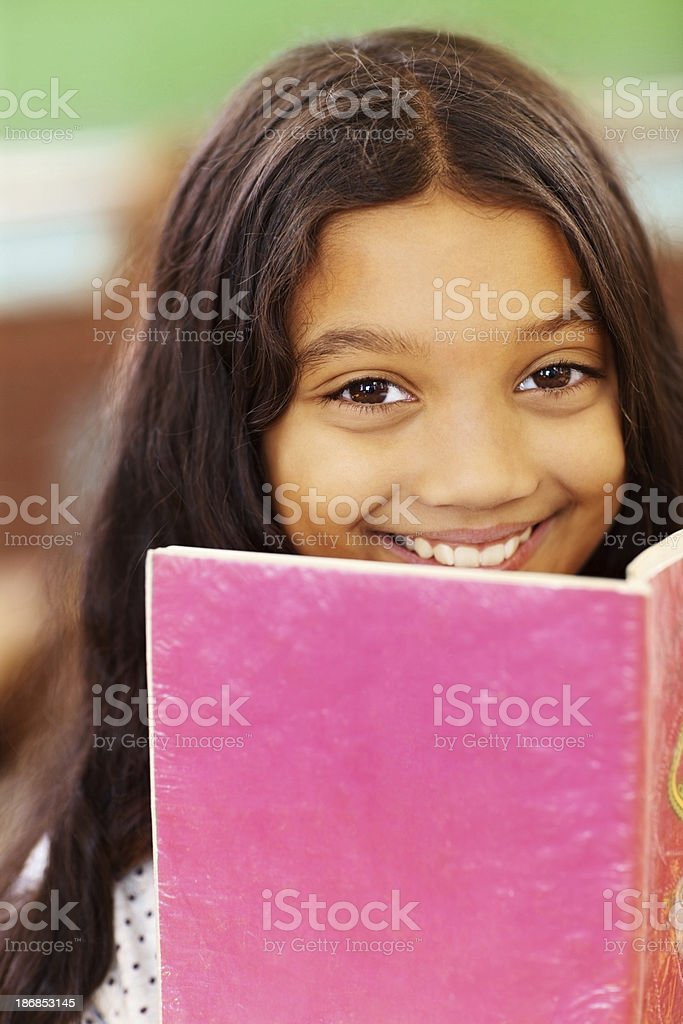 Closeup portrait of a cute school girl reading book royalty-free stock photo