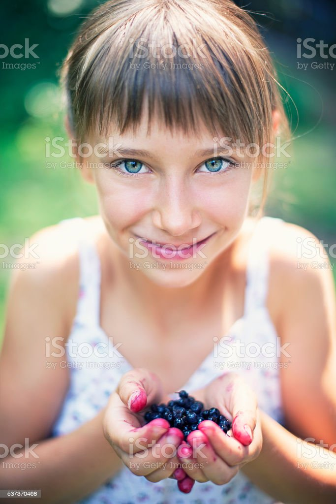 Closeup portrait of a girl holding a handful of blueberries stock photo