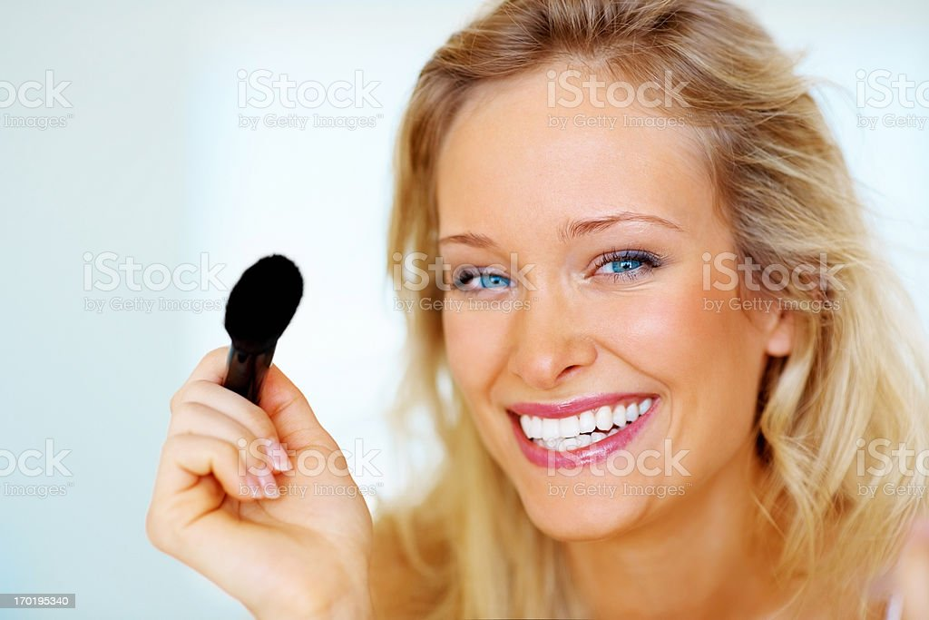 Closeup portrait of a happy beautiful woman applying make up stock photo