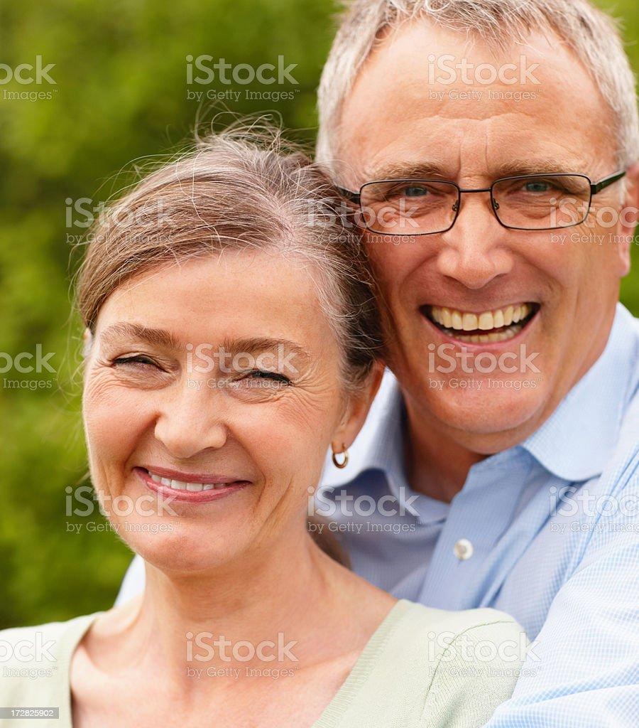 Closeup portrait of a senior couple smiling outdoors stock photo