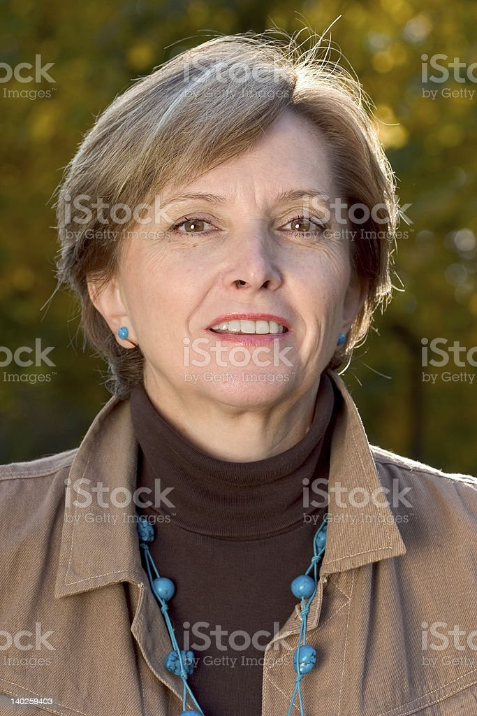 Close-up portrait of a smiling mature woman in autumn royalty-free stock photo