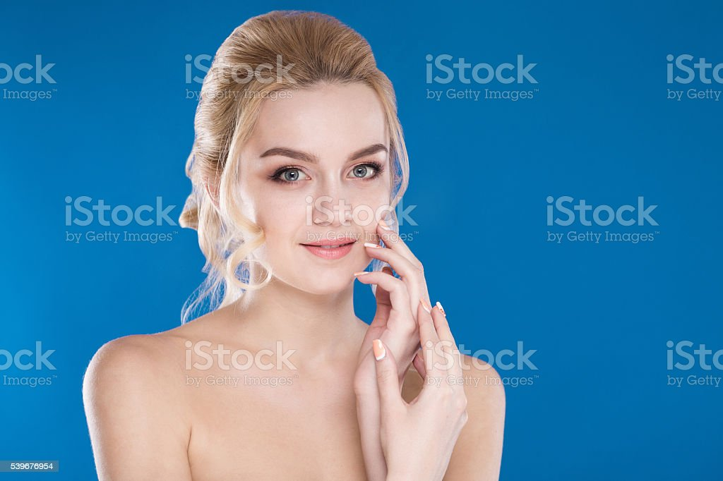 close-up portrait of a young girl on a blue background stock photo