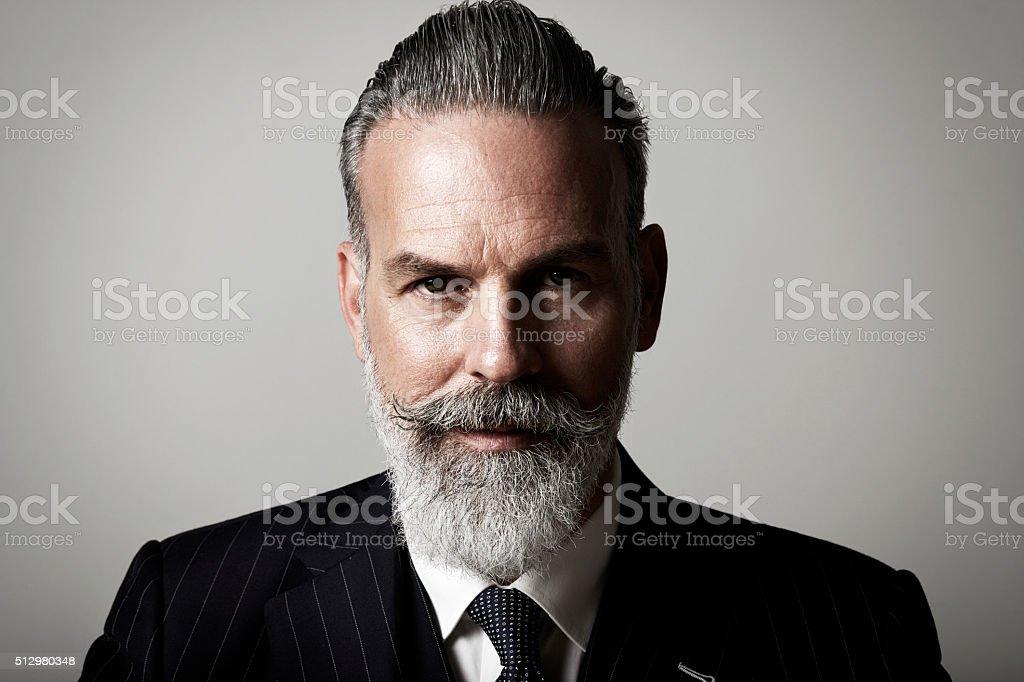 Closeup portrait of adult businessman wearing trendy suit  against the stock photo