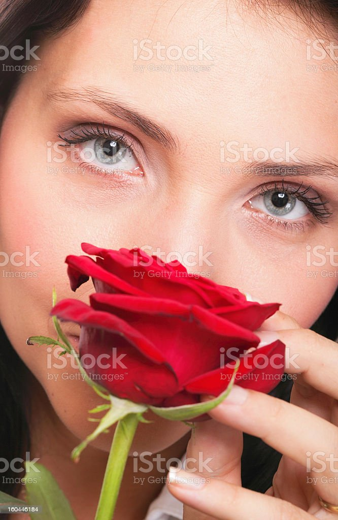 Closeup portrait of attractive young woman holding a red rose royalty-free stock photo