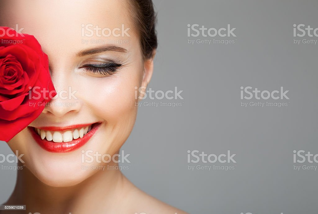 Close-up portrait of beautiful smiling woman with red rose. stock photo