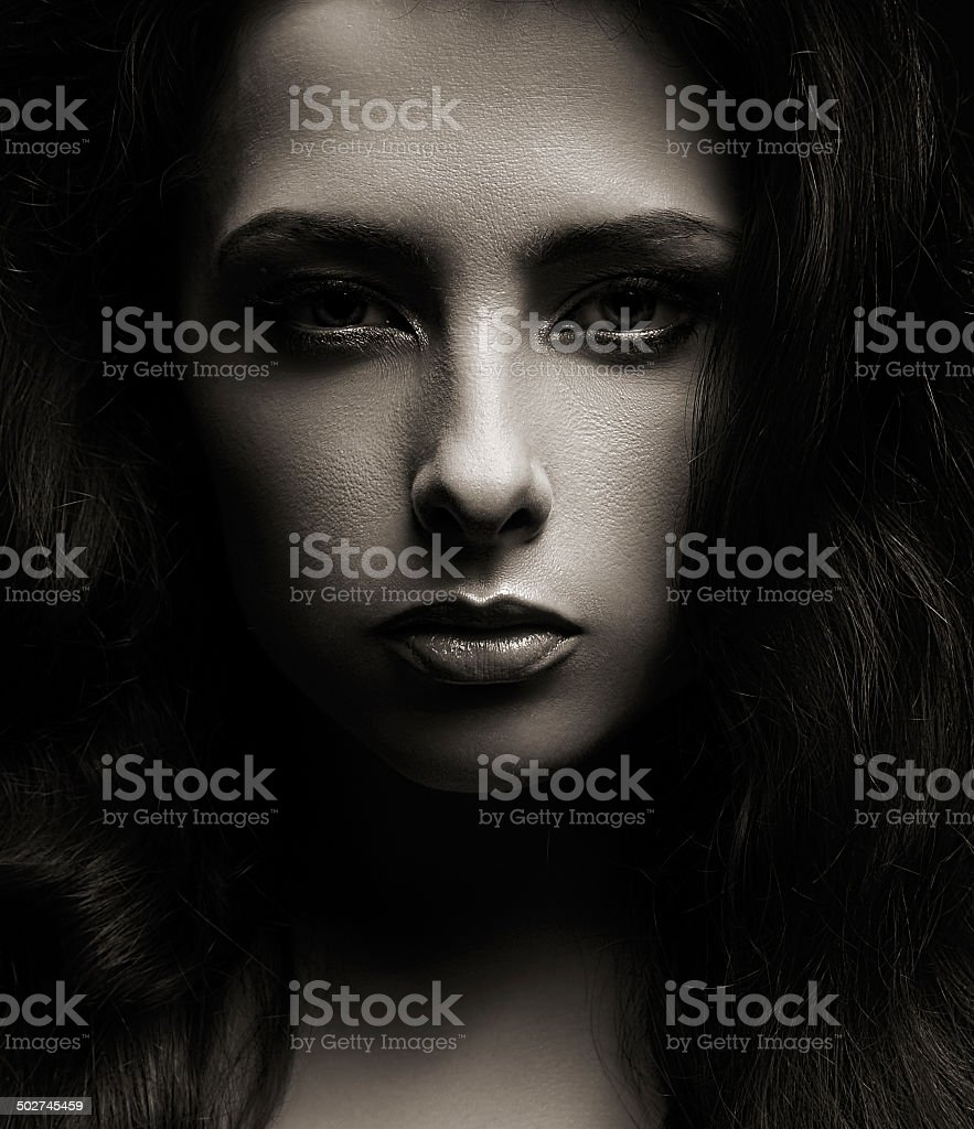 Closeup portrait of beautiful woman face on dark shadows background stock photo