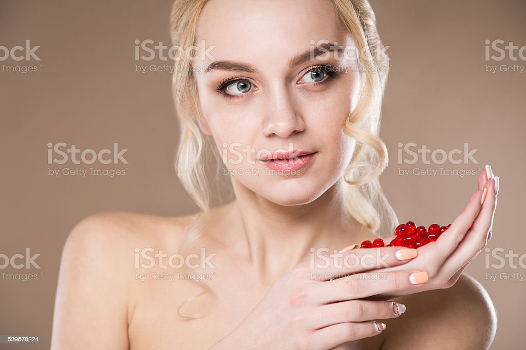 close-up portrait of blonde with red pills in hands stock photo