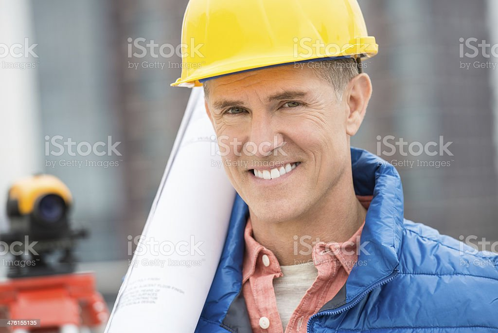 Close-Up Portrait Of Confident With Blueprint royalty-free stock photo