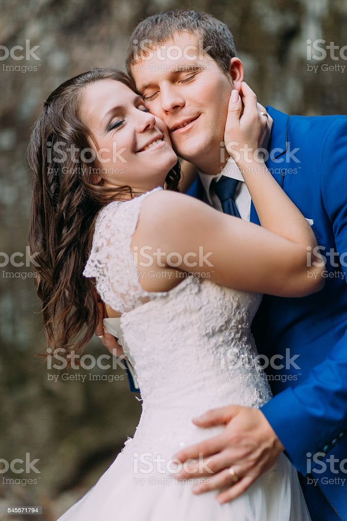 Closeup portrait of happy groom hugging with his bride. Rough stock photo