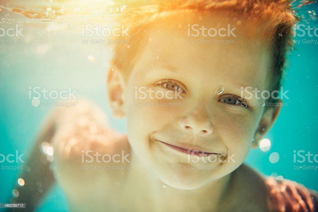 Closeup portrait of little boy swimming underwater in pool stock photo