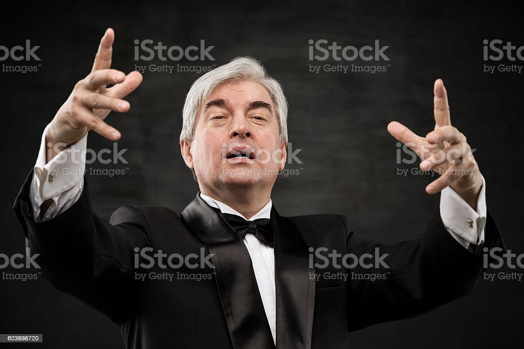 Closeup portrait of male orchestra conductor directing with his hands stock photo