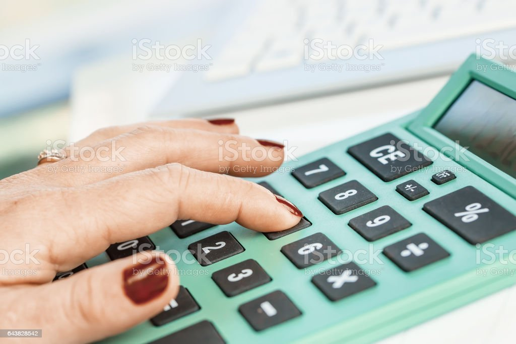 Close-up portrait of red nails businesswoman hand while using calculator. stock photo