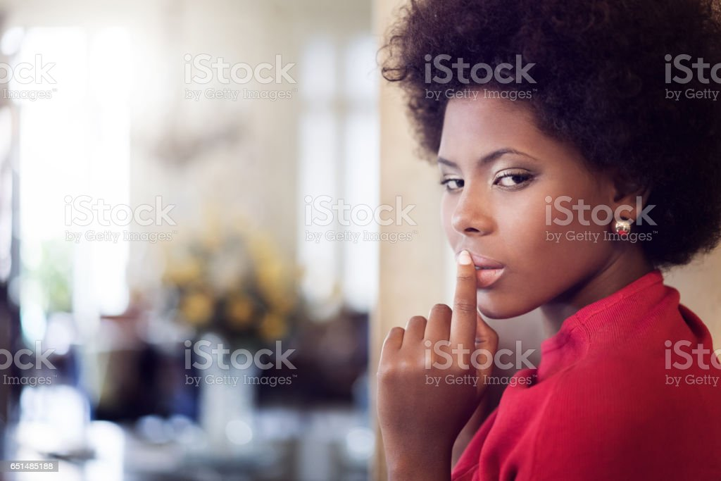 Close-up portrait of seductive woman with finger on lips at home stock photo