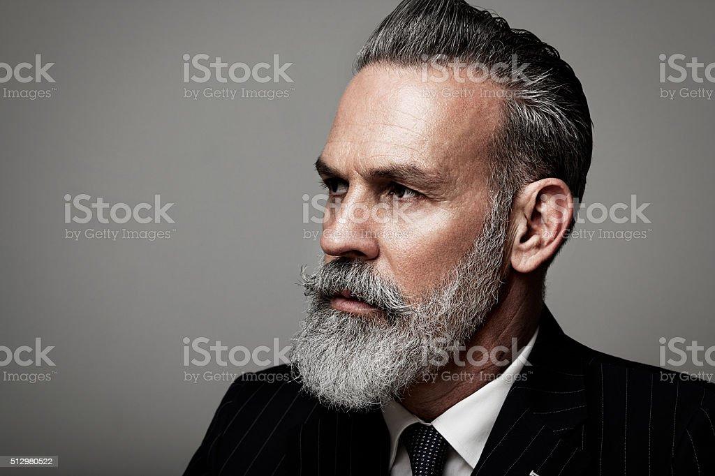 Closeup portrait of serious adult businessman wearing trendy suit  against stock photo
