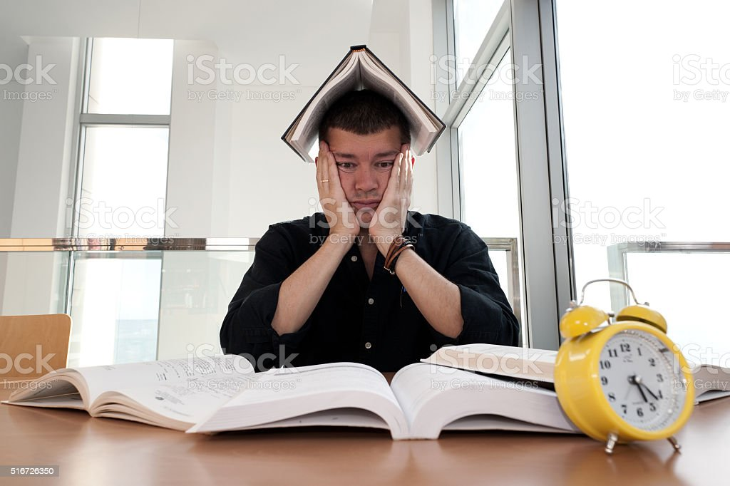 Closeup portrait of stressed man surraunded by books, alarm clock stock photo