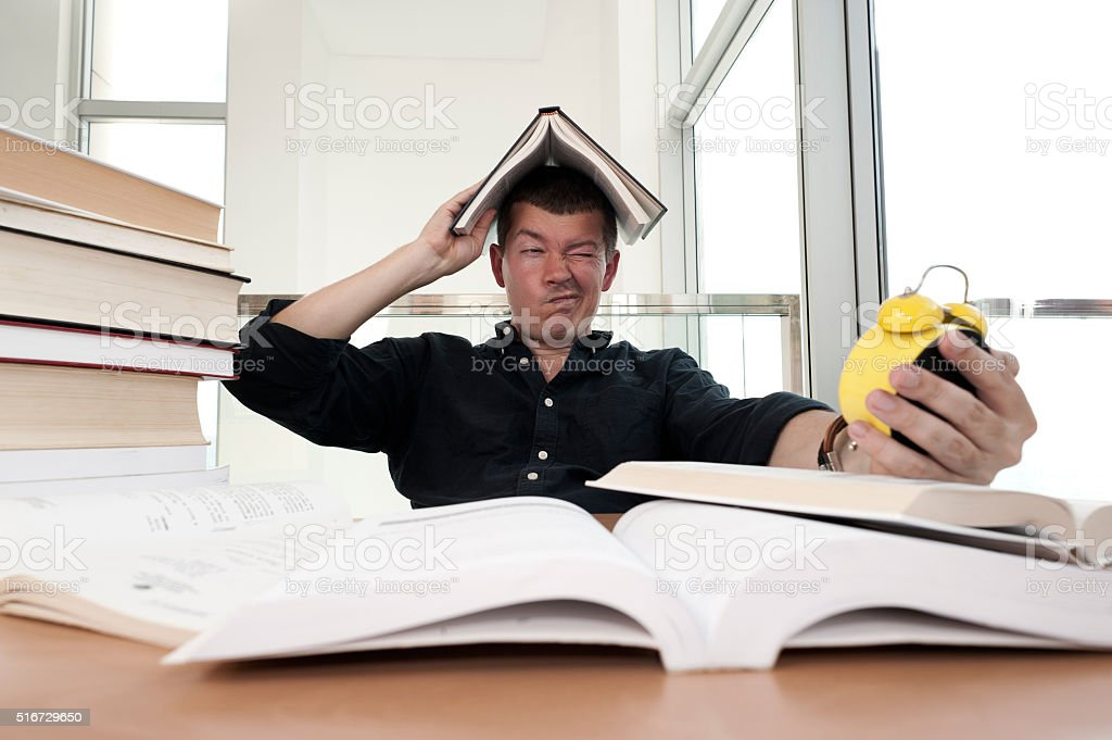 Closeup portrait of stressed man surrounded by books, alarm clock stock photo