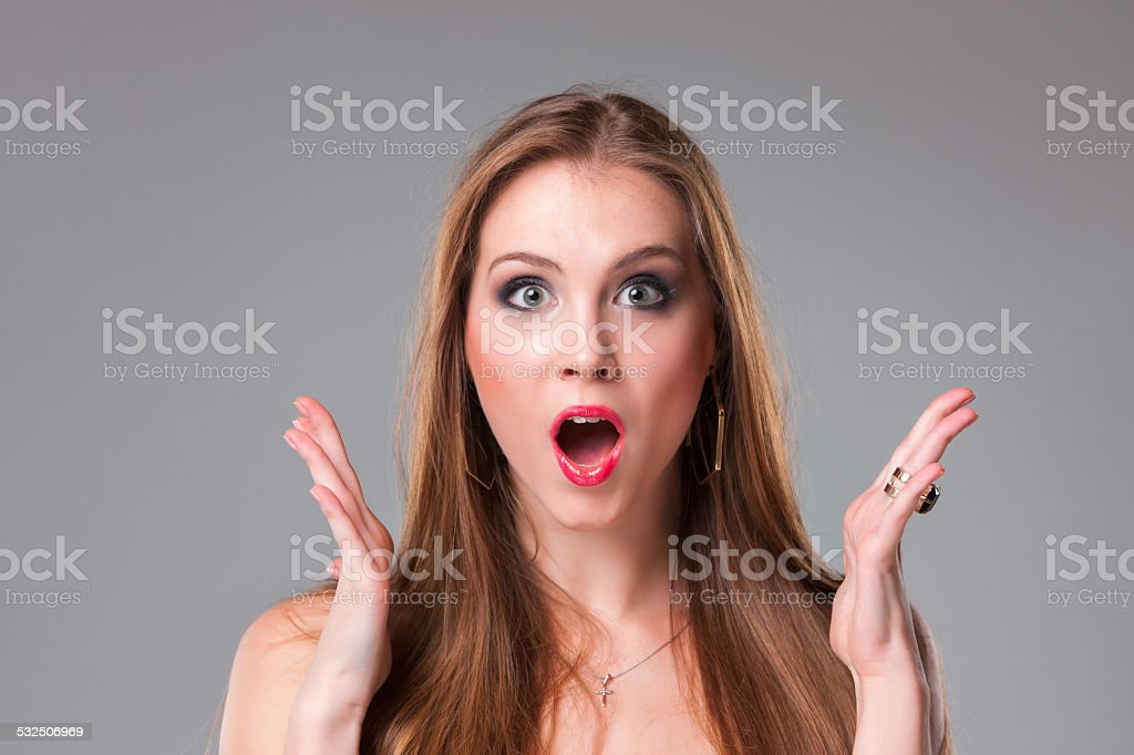 Close-up portrait of surprised beautiful girl holding her head stock photo