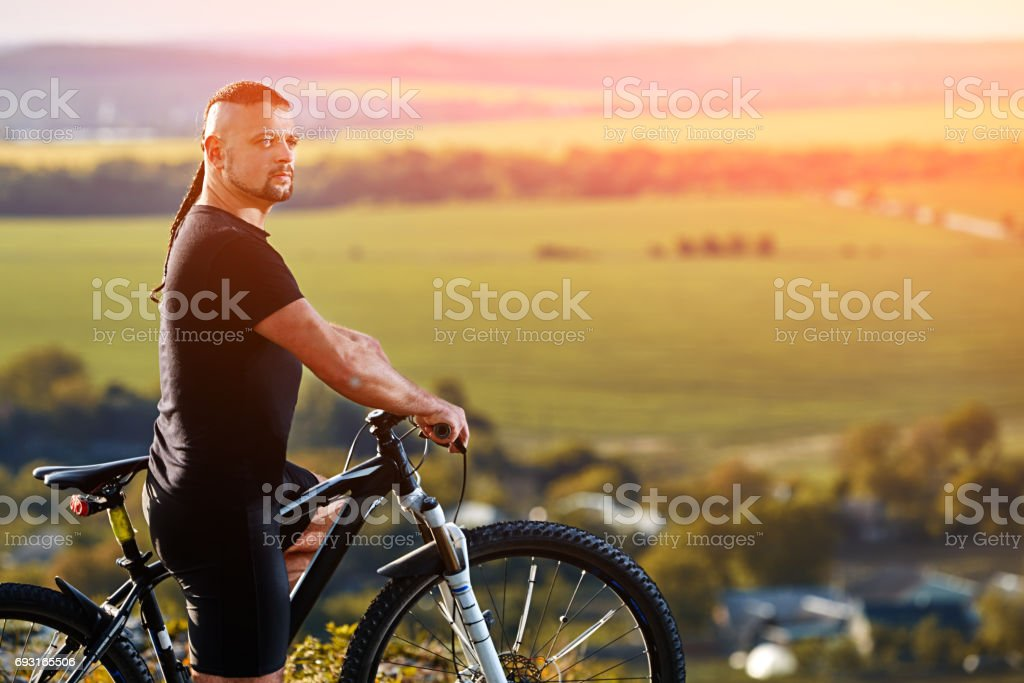 Close-up portrait of the mountain biker looking at beautiful landscape. stock photo