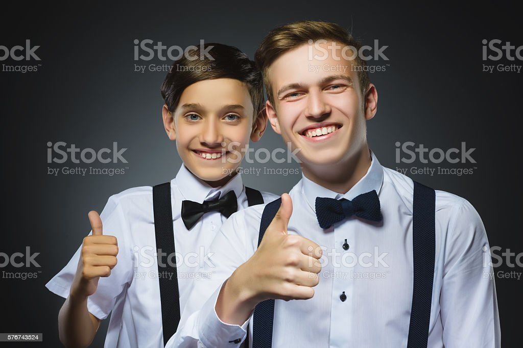 Closeup portrait of two successful happy boys show thumbs up stock photo