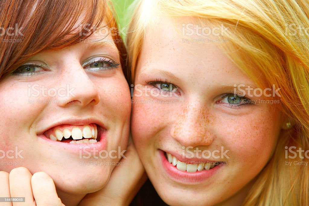 Closeup portrait of two young female friends smiling royalty-free stock photo