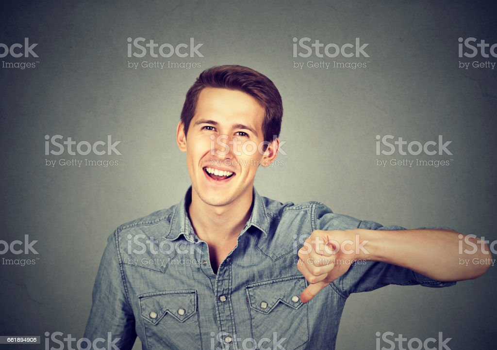 Closeup portrait sarcastic young man showing thumbs down stock photo