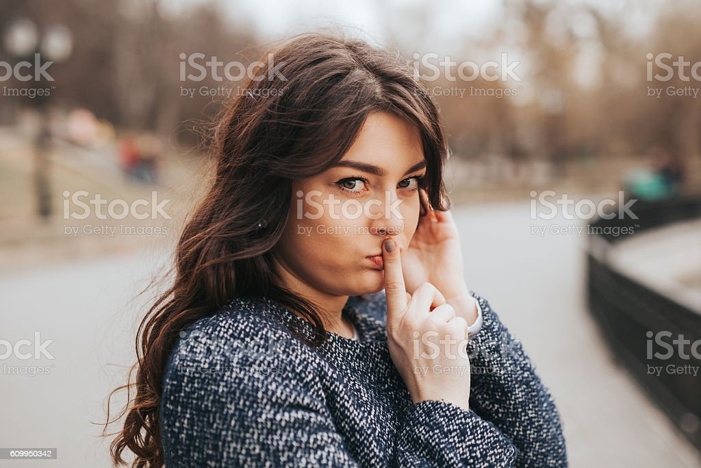 Closeup portrait secretive young woman placing finger on lips stock photo
