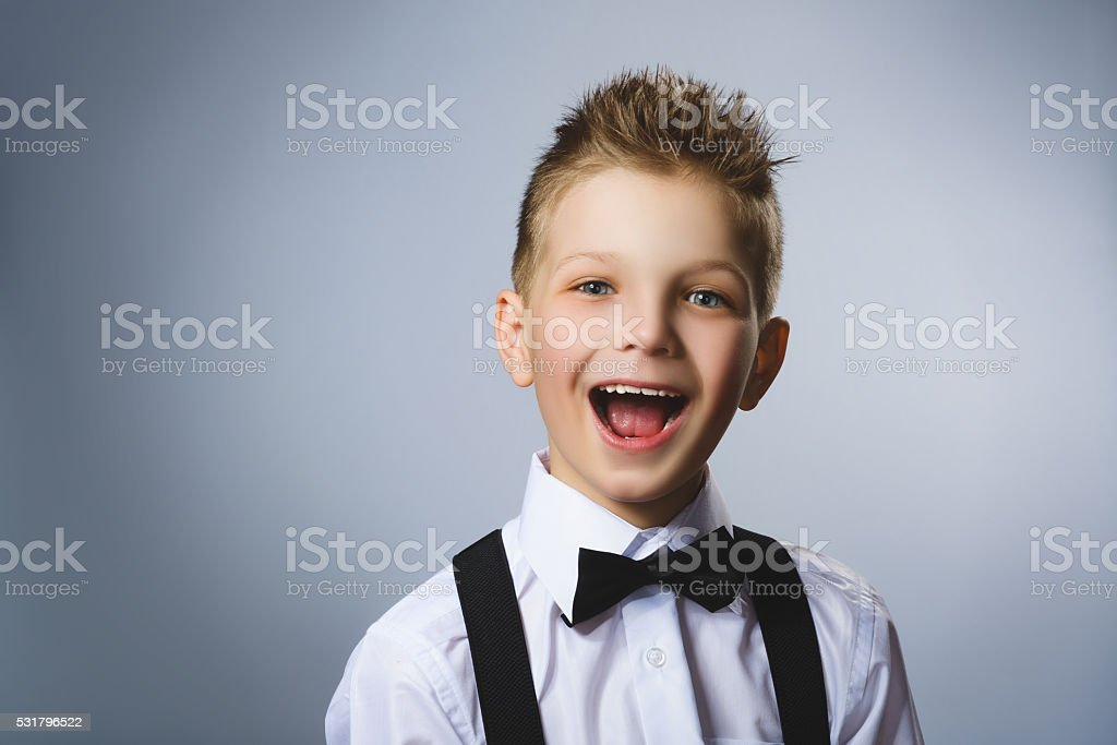 Closeup portrait successful happy boy isolated grey background. Positive human stock photo