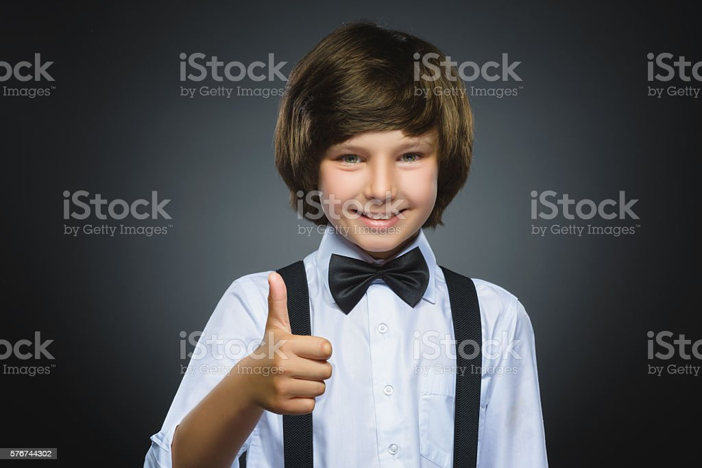 Closeup portrait successful happy boy show thumb up isolated grey stock photo