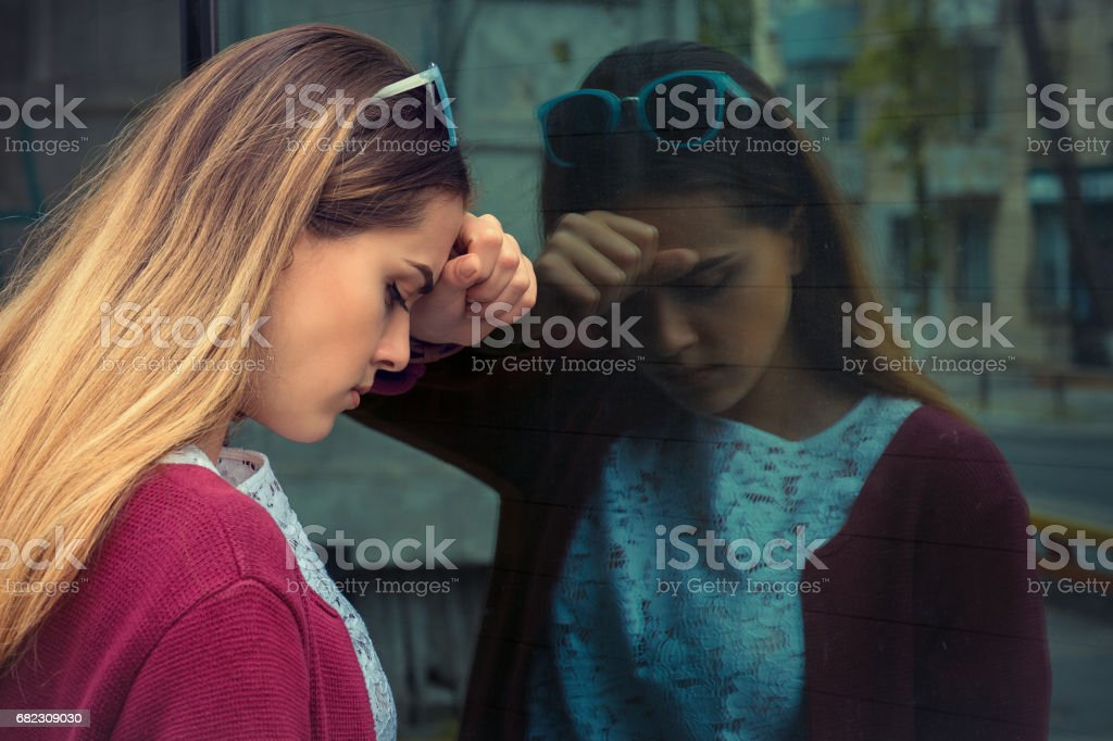 Closeup portrait unhappy young business woman, head on window, bothered by mistake having bad headache isolated background corporate office. Negative human emotion, facial expression life reaction stock photo