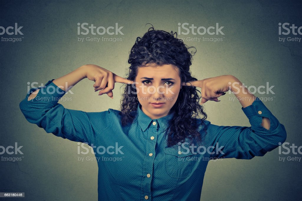 Closeup portrait upset woman plugging ears with fingers doesn't want to listen stock photo