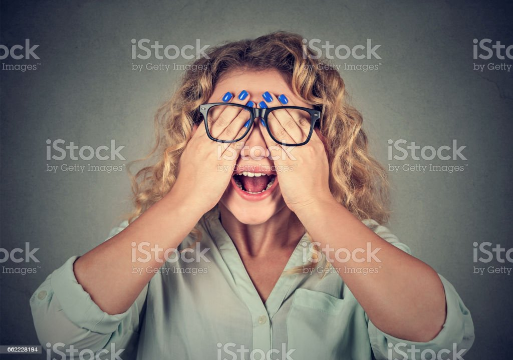 Closeup portrait woman in glasses covering face stock photo