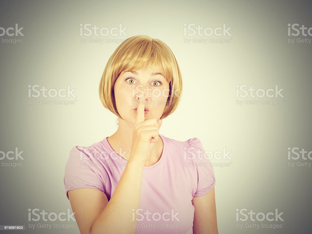 Closeup portrait young woman placing finger on lips stock photo