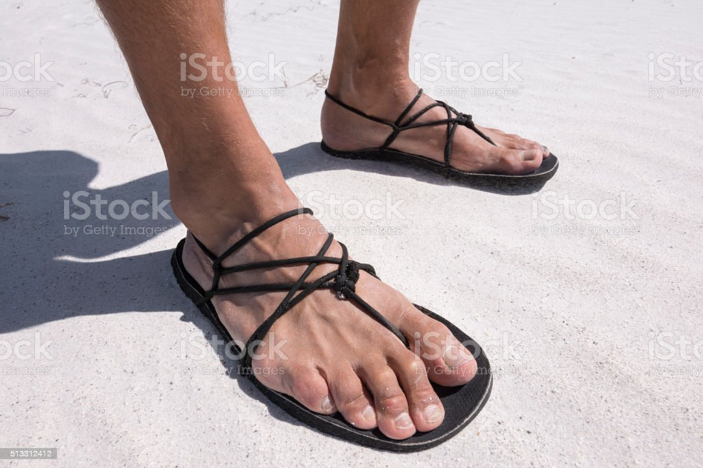 Closeup primitive sandals worn on beach stock photo