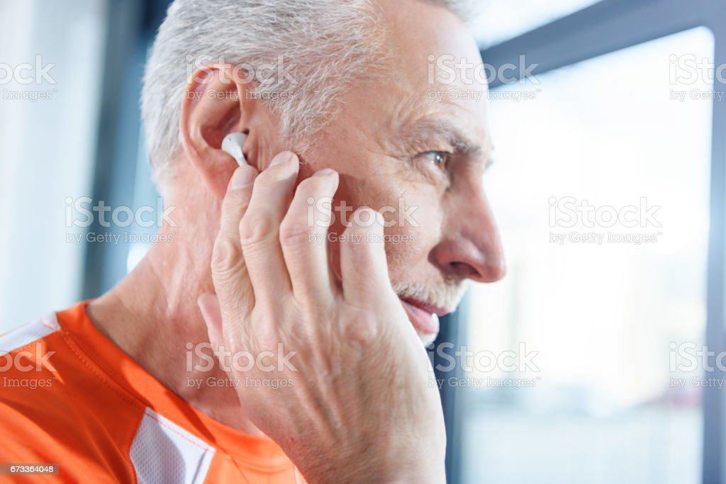 Close-up profile portrait of bearded mature man in earphones looking away stock photo