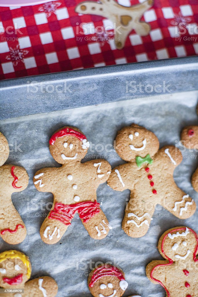 Close-up Raw gingerbread men with glaze on a baking sheet stock photo
