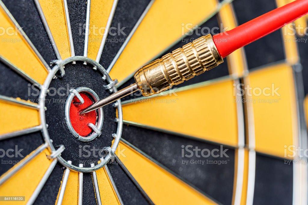 closeup red dart arrow hitting in target bullseye of dartboard stock photo