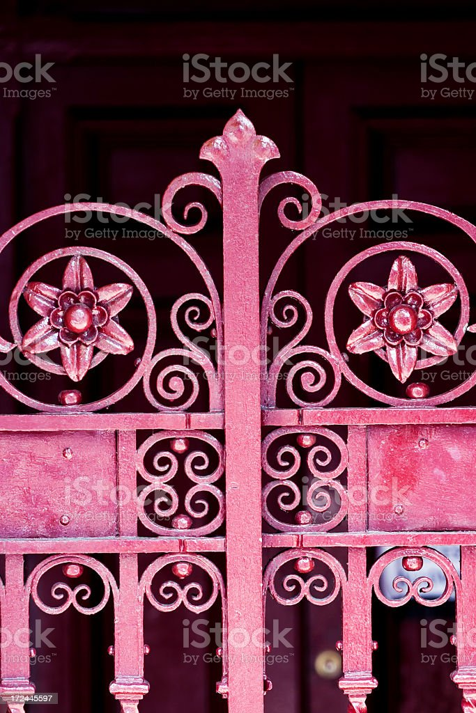 Closeup red iron ornate gate against dark background, copy space royalty-free stock photo