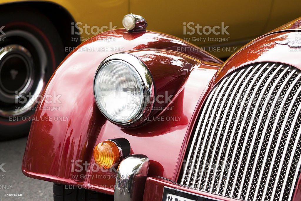 Closeup red Morgan car headlight and radiator grille stock photo