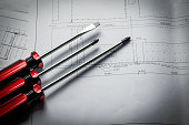 closeup red screwdriver work equipment with diagram paper plan
