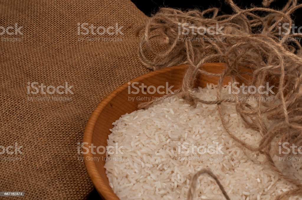 Closeup rice in wooden bowl with wooden spoon on black background empty space stock photo