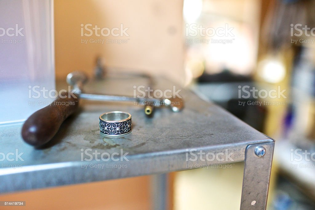 Close-up ring with silver-black design at jewelry workshop stock photo