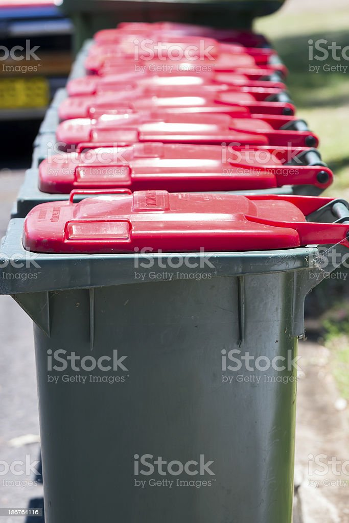 Closeup row of plastick green rubbish bins with red lids royalty-free stock photo