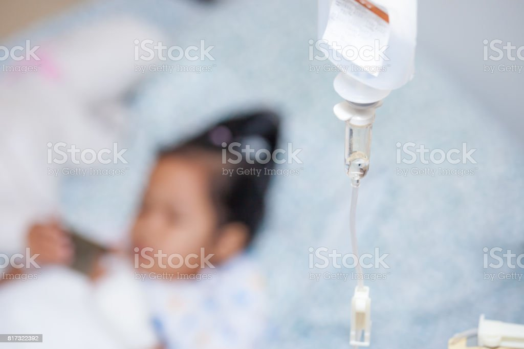 Closeup saline IV drip for patient and Infusion pump feeding into child patient stock photo