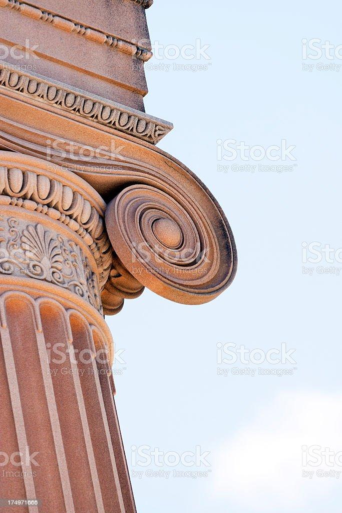 Closeup sandstone ornate column against blue sky, copy space royalty-free stock photo